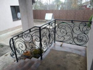 Оздоблення тераси та сходів огорожденням з різнестороніми завитками.